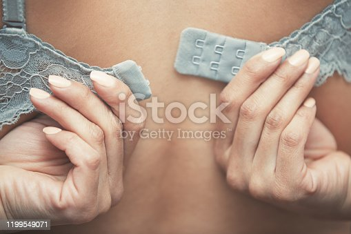 Woman dressing brassiere. Close-up rear view photo