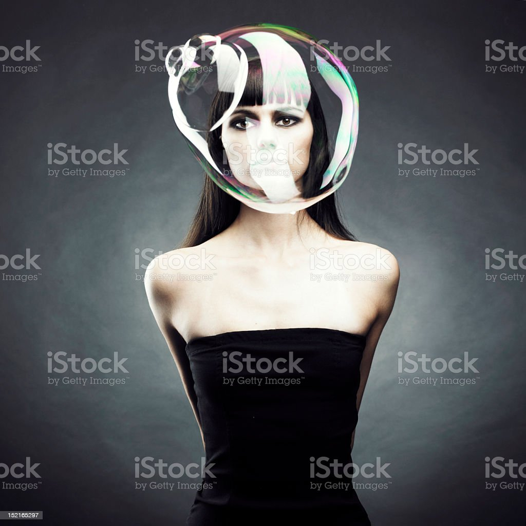 Woman dressing in black blowing a large soap bubble stock photo