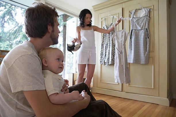 frau dressing mit mann und baby mädchen (6-9 monate - mutterkleiderschrank stock-fotos und bilder