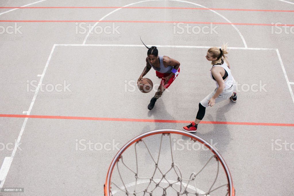 Woman dribling and playing  basketball with friend stock photo