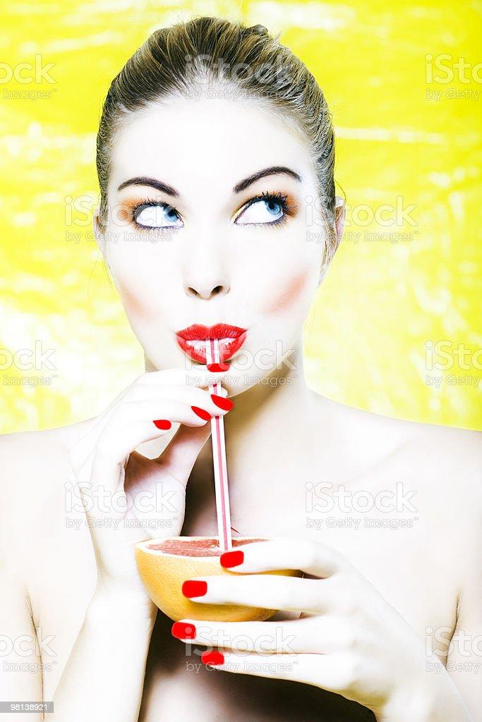 woman driking orage grapefruit citrus fruit juice with straw royalty-free stock photo
