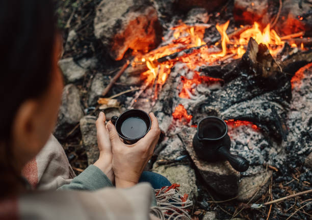 Woman drink a coffee near campfire stock photo