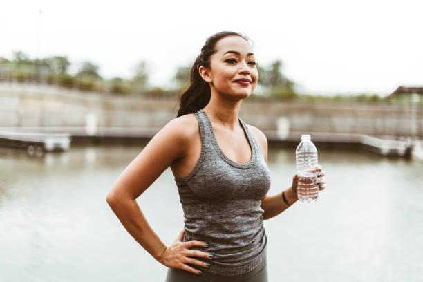boire de l'eau de femme après la formation - brassière de sport photos et images de collection