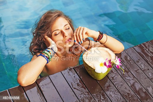 istock Woman drinking a coconut cocktail with closed eyes 492454558