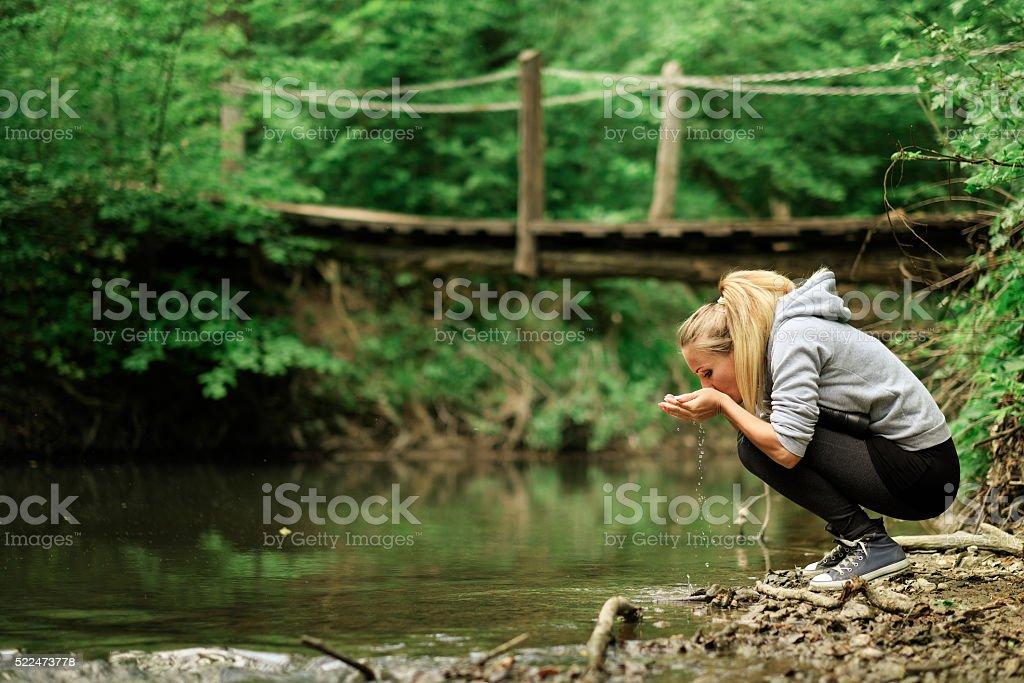 Frau trinkt eine Wasser Bach – Foto