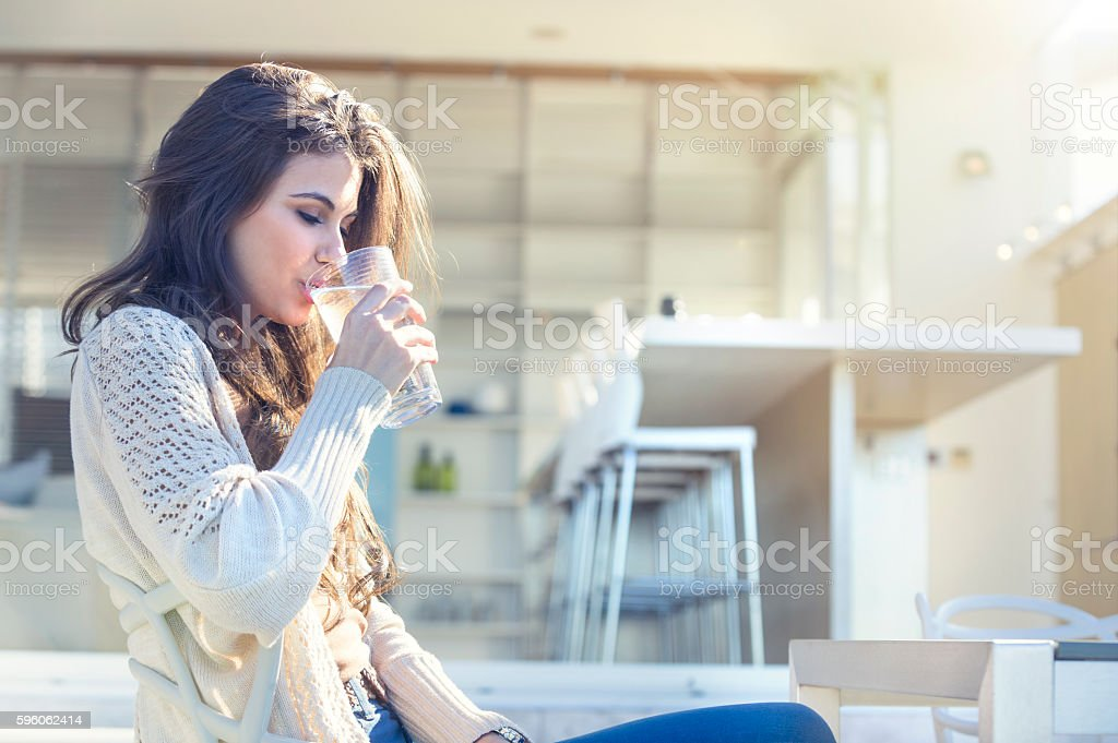 Woman drinking a glass of water. stock photo