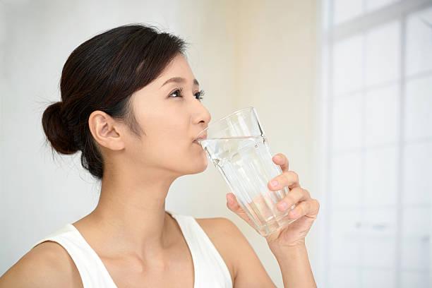 frau trinkt ein glas wasser - wasser trinken abnehmen stock-fotos und bilder