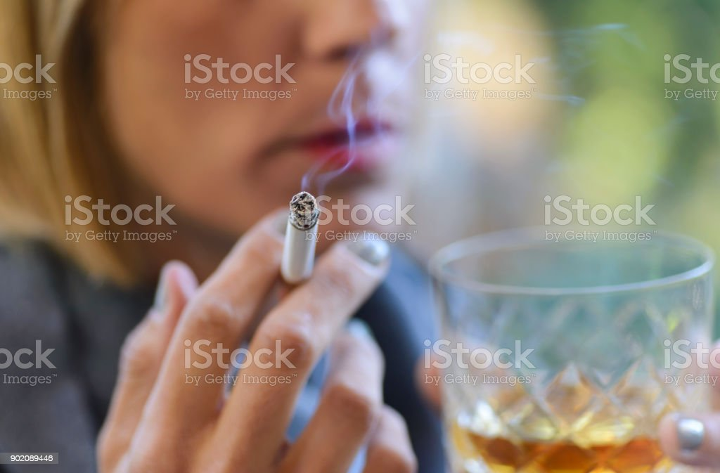 Woman drinking a glass of whiskey and smoking a cigarette. stock photo