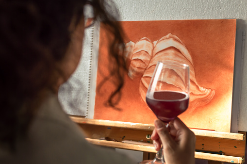 istock Woman drinking a glass of wine to celebrate that she has finished her painting. Artist contemplating his finished work. 1162220981