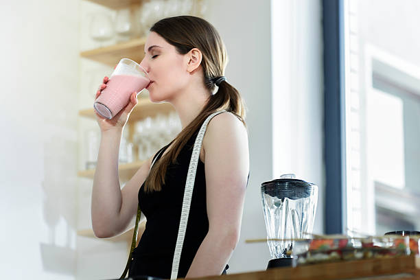 woman drinking a meal replacement shakes - milkshake stockfoto's en -beelden
