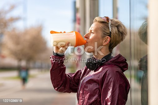 A woman in sports clothing drinking a protein shake. She is wearing a pair of headphones around her neck and a pair of sunglasses on her head.