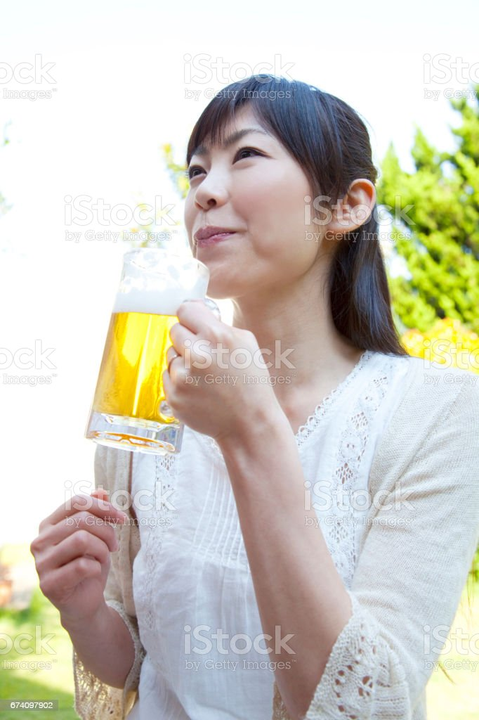 Woman drinking beer in the garden royalty-free stock photo