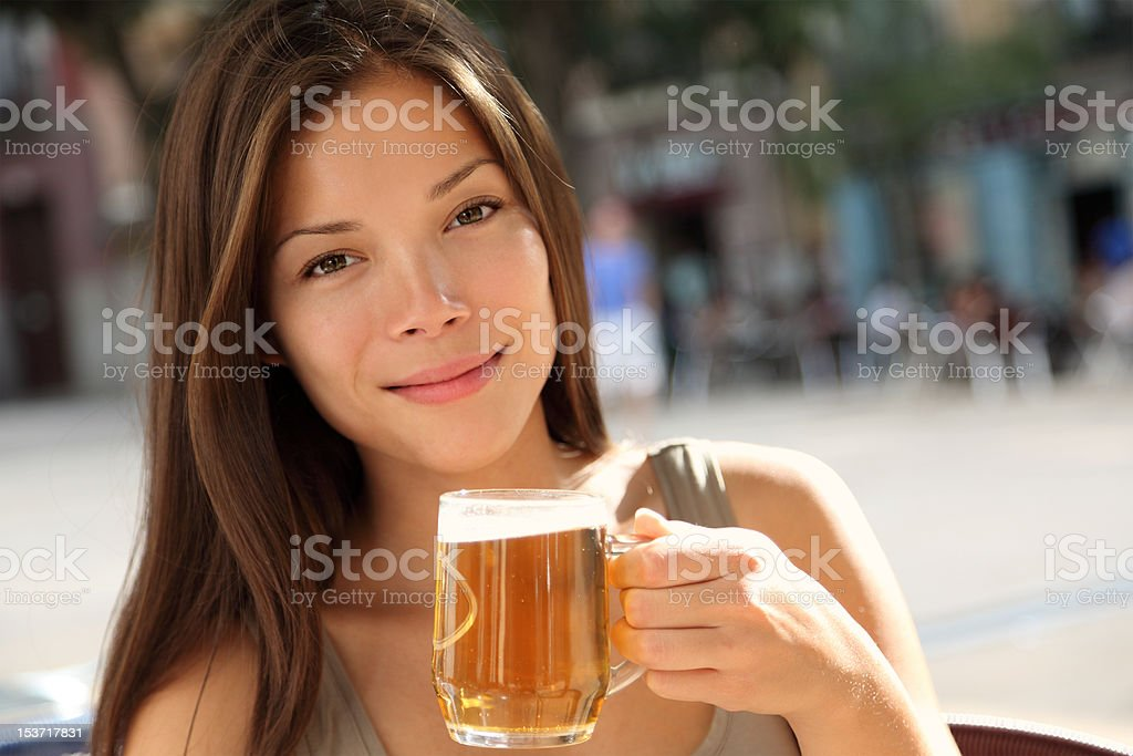 Woman drinking beer on a terrace cafe stock photo