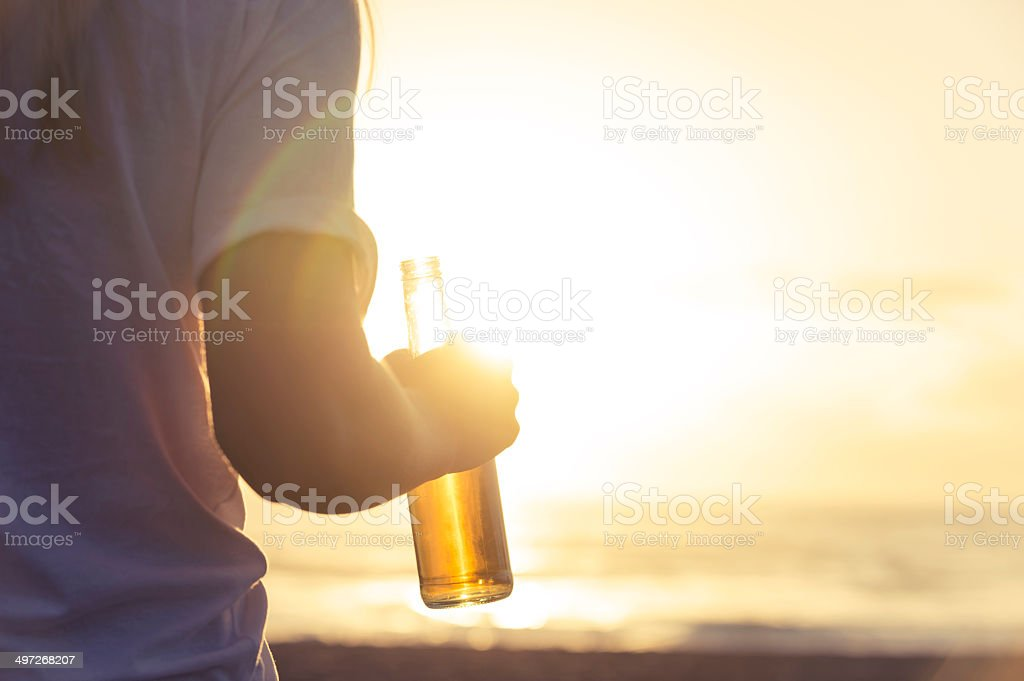 Woman drinking beer on the beach stock photo