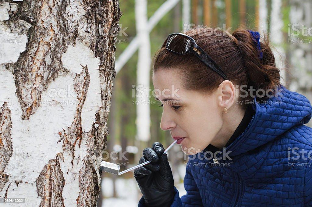 Woman drinking birch sap foto