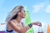 Woman drinking bottle of water on the beach