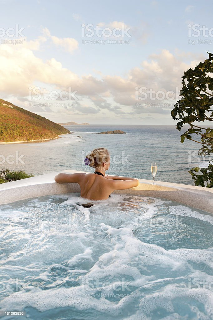 woman drinking champagne in a jacuzzi enjoying Caribbean view stock photo