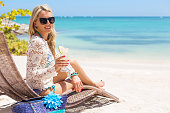 istock Woman drinking cocktail and relaxing in chair on the beach 479101106