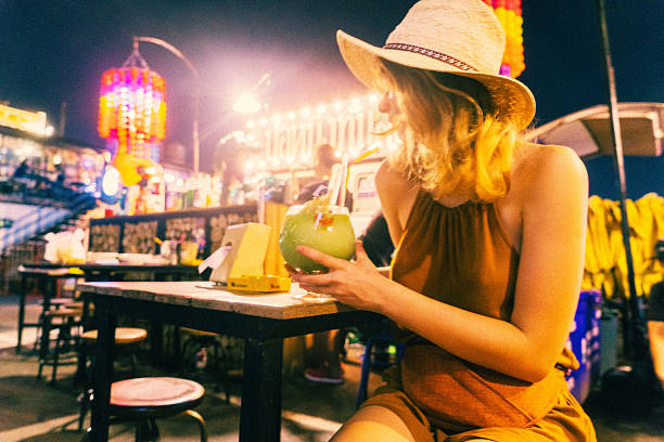 Woman drinking cocktail at night Young Caucasian woman drinking cocktail at night  in Bangkok night market  night market stock pictures, royalty-free photos & images