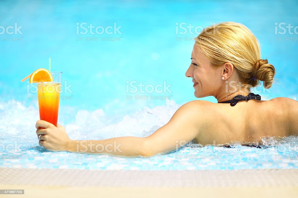 Woman drinking cocktail by the pool. royalty-free stock photo