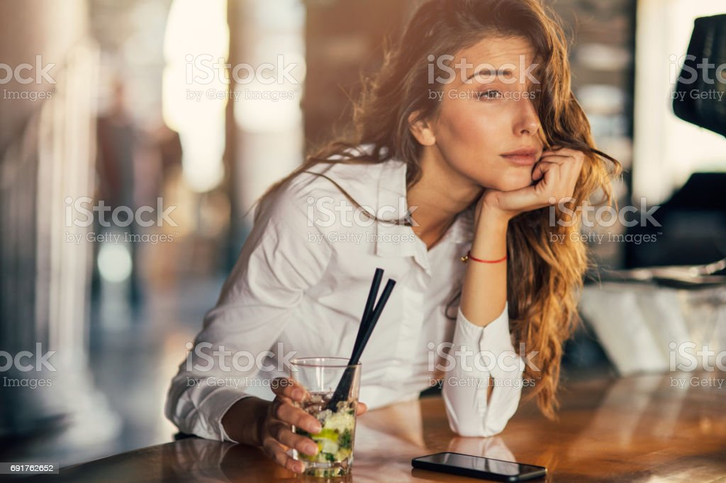 Woman drinking cocktail in a bar stock photo