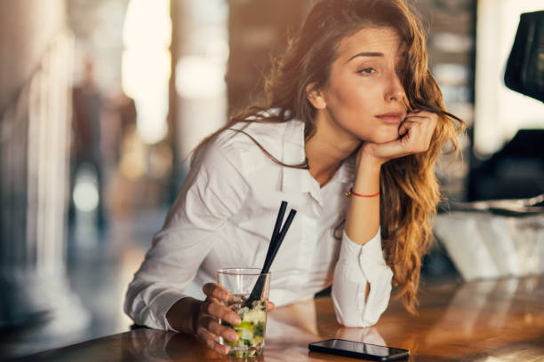 woman drinking cocktail in a bar - drunk stock photos and pictures