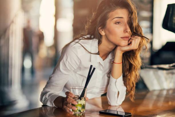 Femme buvant cocktail dans un bar - Photo