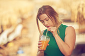 istock woman drinking cocktail on the beach 1128215845