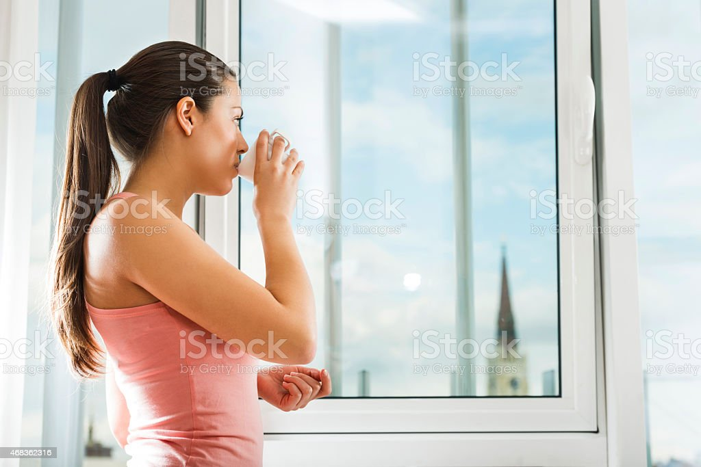 Woman drinking coffee and looking through the window. royalty-free stock photo