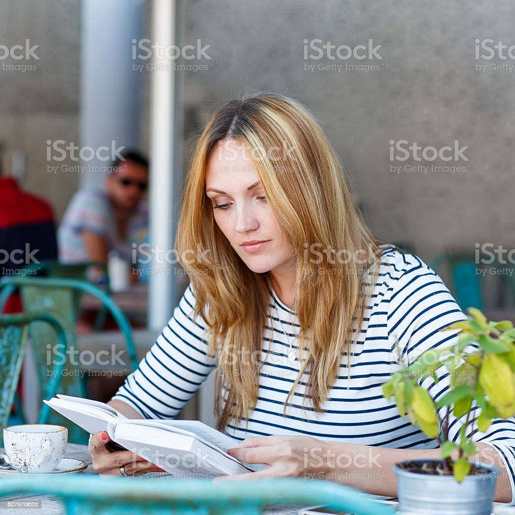 Woman drinking coffee and reading book in cafe stock photo