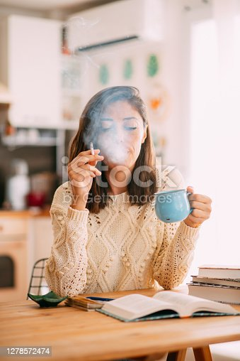 Woman Drinking Coffee and Smoking While Reading Book at Home