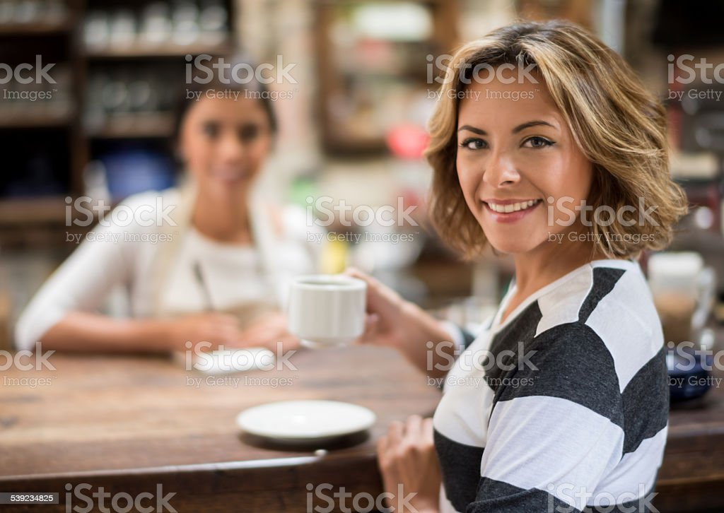 Woman drinking coffee at a cafe royalty-free stock photo