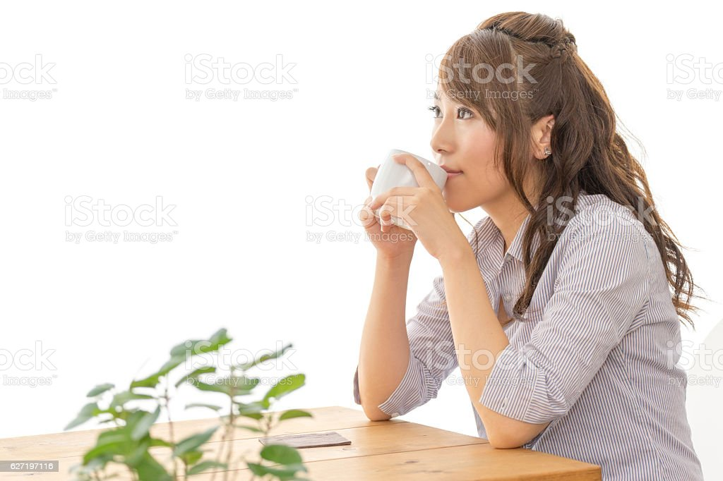 Woman drinking coffee at a cafe stock photo