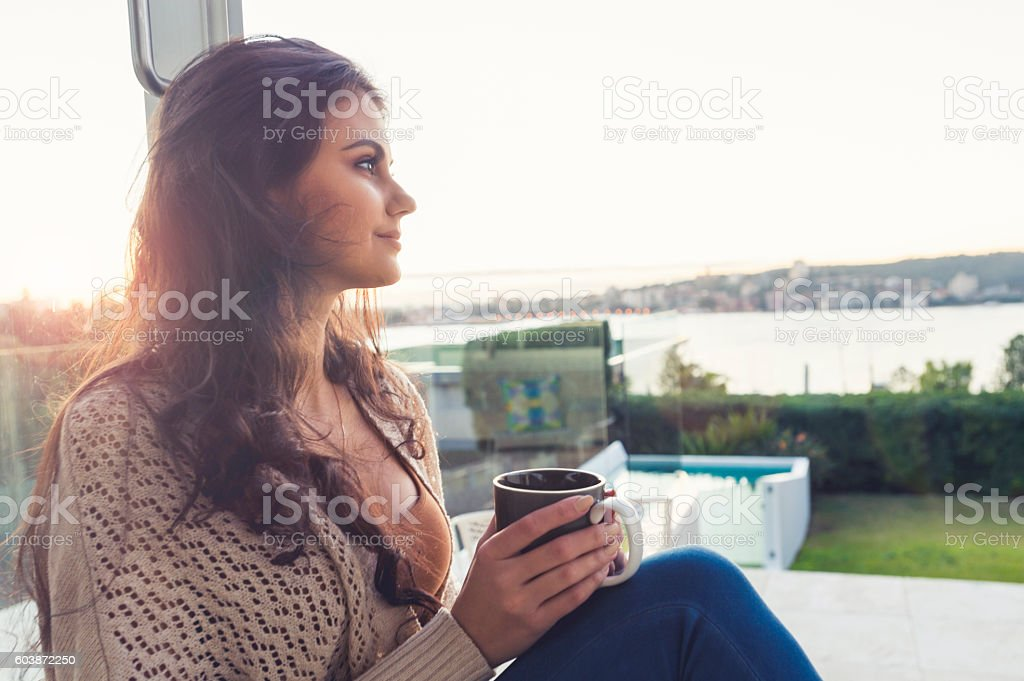 Woman drinking coffee at sunrise. stock photo