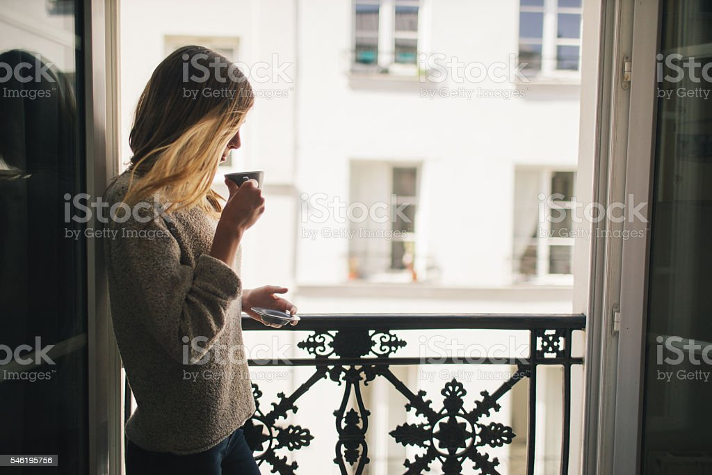 Woman drinking coffee at the balcony stock photo