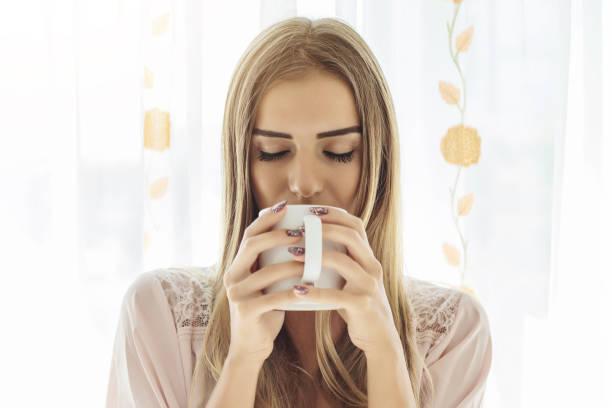 frau trinkt kaffee am fenster - grüner tee koffein stock-fotos und bilder