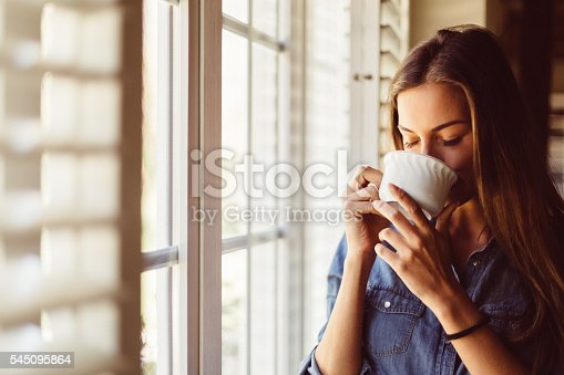 Young woman with coffee cup near the window