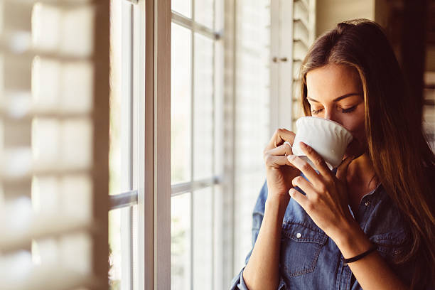 Woman drinking coffee early in the morning stock photo