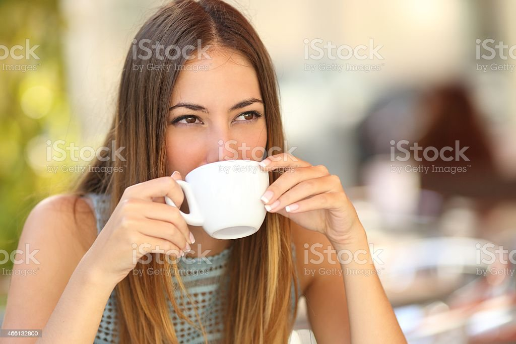 Woman drinking a coffee from a cup in a restaurant terrace while...