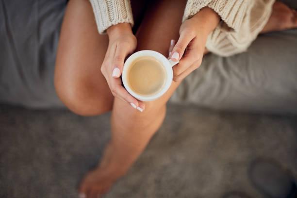 Frau trinkt Kaffee im Bett. – Foto