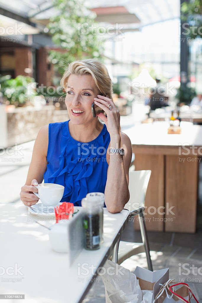 Woman drinking coffee in cafe and talking on cell phone royalty-free stock photo