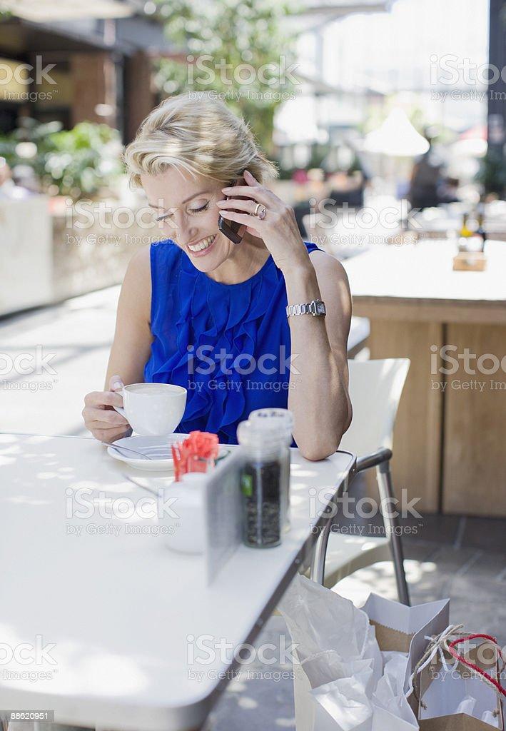 Femme buvant un café au Café et de parler sur téléphone portable photo libre de droits