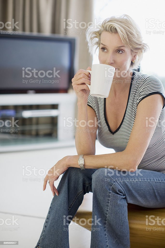 Woman drinking coffee in living room royalty-free stock photo
