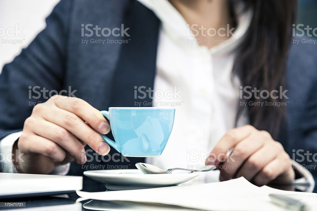 Woman drinking coffee in office royalty-free stock photo