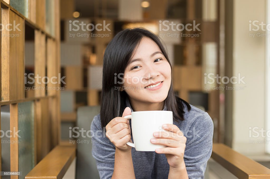 Woman drinking coffee in the morning at cafe stock photo