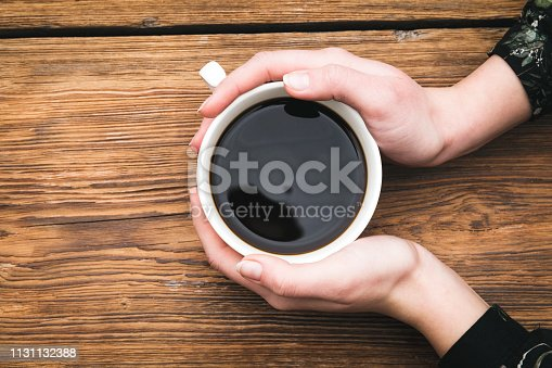 Close up of woman drinking coffee on wooden table
