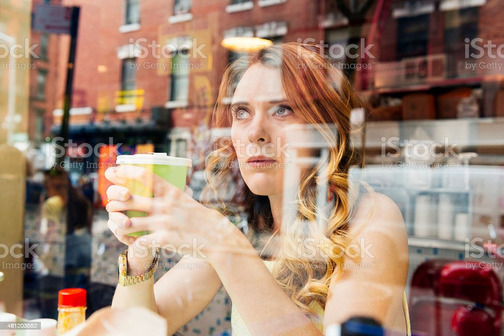 NYC Woman Drinking Coffee Looks Out Window at Cafe Restaurant This is a horizontal, color, royalty free stock photograph of a white British feminine woman living in New York City. She spends time in urban Manhattan on a summer day in the SoHo area. She sits at a small cafe restaurant. She sits at a counter holding a cup of coffee and looking out a window facing the sidewalk. The architecture from the buildings across the street are reflected on the window. Photographed from outside with a Nikon D800 DSLR camera. 20-29 Years Stock Photo