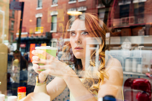 Nyc Woman Drinking Coffee Looks Out Window At Cafe Restaurant Stock Photo - Download Image Now