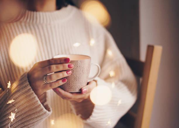 frau trinkt kaffee an einem kalten wintertag - herbst nagellack stock-fotos und bilder