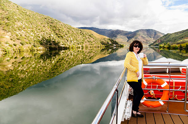Woman drinking coffee on a river cruise An adult woman is enjoying a cup of coffee while on a river cruise down the Douro River, Portugal. duero stock pictures, royalty-free photos & images